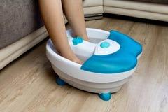 在一个振动的脚按摩器的脚 电按摩浴 在修脚前的脚浴 库存照片