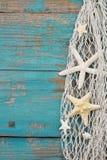在一个捕鱼网的海星有绿松石木背景, po 免版税库存图片