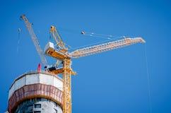 在一个摩天大楼顶部的两台黄色起重机建设中蓝色清楚的天空的 免版税库存图片