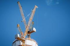 在一个摩天大楼顶部的两台黄色起重机建设中蓝色清楚的天空的 图库摄影