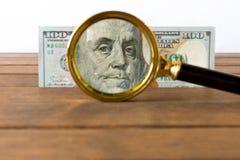 100在一个放大镜下的美金在一张木桌上 的treadled 库存图片