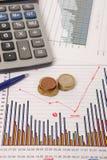 在一个文件的硬币与有些图表 免版税库存照片