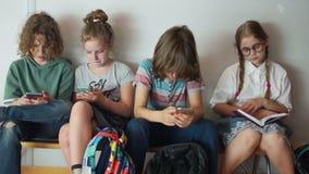 在一个断裂期间的儿童学童在学校 学生为在学校走廊,期末考试的检查做准备 股票录像