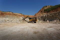在一个新建工程站点的一种大黄色挖掘机蓝天和含沙猎物背景的 复制空间 复制空间 免版税库存图片
