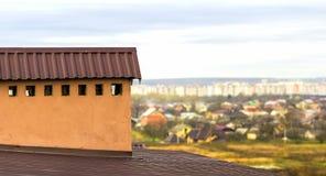 在一个新的建造的房子的屋顶的烟囱有下面城市的看法 免版税库存照片
