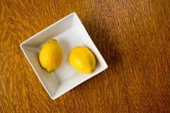 在一个方形的碗的两个柠檬 免版税库存图片