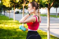 在一个早晨在夏天城市后,跑女孩听到在耳机的音乐并且喝从振动器的蛋白质 库存照片
