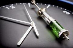 在一个时钟的一个注射器在实验室 库存照片