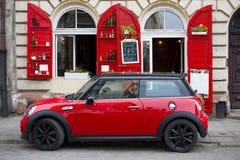 在一个时髦的大厦的背景的红色汽车 免版税库存图片