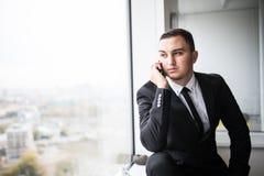 在一个时髦的现代办公室空间的商人与大窗口,谈话在电话 免版税库存图片