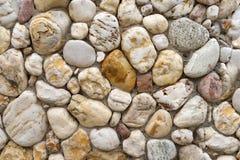 在一个明亮的石墙的小卵石石头 图库摄影