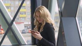 在一个明亮的窗口附近的美丽的白肤金发的女孩享用电话并且拨消息 库存照片
