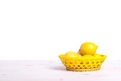 在一个明亮的篮子的柠檬在隔离桌侧视图  免版税库存图片
