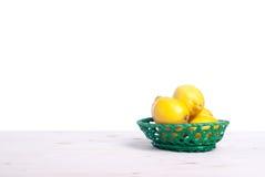 在一个明亮的篮子的柠檬在隔离桌侧视图  免版税库存照片