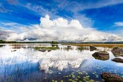 在一个明亮的蓝色湖的剧烈的白色云彩 免版税图库摄影