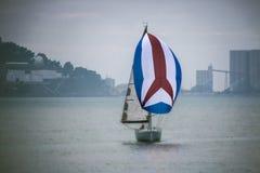 在一个明亮的风帆下的一条美丽的游艇在多云天气的海 免版税图库摄影