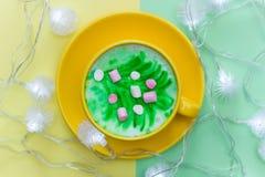 在一个明亮的黄色杯子的彩虹热奶咖啡 库存照片