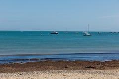 在一个春日拍的照片在看往在海的小船的Swanage海滩 图库摄影