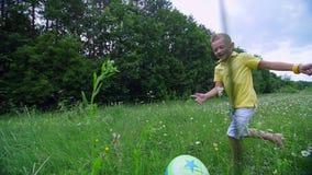 在一个春黄菊草甸,在森林附近,男孩,孩子,戏剧球,投掷它,追捕他 他获得乐趣 夏天 股票视频