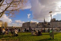 在一个晴天春天期间,游人在塞纳河的银行喝并且去野餐在巴黎, 库存图片