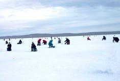 在一个晴朗的冬日,有渔夫坐一个大湖 免版税库存照片