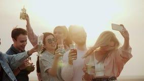 在一个晴朗的屋顶的夏天,一个小组朋友获得乐趣,饮料夏天都市鸡尾酒并且采取selfies微笑 股票录像