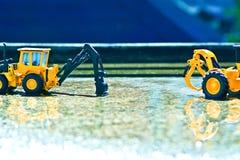 在一个有一点湿水泥地板上的两个folklene玩具在春雨中在水中有一点发光 库存图片