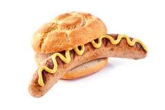 在一个有壳的面包小圆面包的多味腊肠用黄色芥末 库存照片