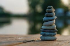 在一个有薄雾的湖旁边的禅宗平衡的小卵石 免版税图库摄影