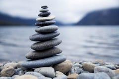 在一个有薄雾的湖概念旁边的禅宗平衡的小卵石 免版税库存照片