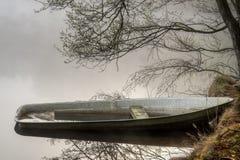 在一个有薄雾的湖的小船。 库存图片