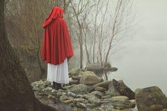在一个有薄雾的湖的岸的小红骑兜帽 免版税库存照片