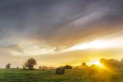 在一个有薄雾的草甸的日出有秸杆块的 图库摄影