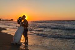在一个朦胧的海滩的结婚的年轻夫妇在黄昏 免版税库存照片