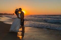 在一个朦胧的海滩的结婚的年轻夫妇在黄昏 图库摄影