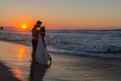 在一个朦胧的海滩的结婚的年轻夫妇在黄昏 库存图片