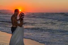 在一个朦胧的海滩的结婚的年轻夫妇在黄昏 库存照片