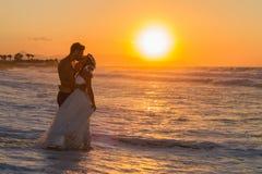 在一个朦胧的海滩的结婚的年轻夫妇在黄昏 免版税库存图片