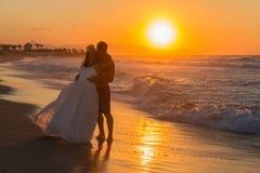 在一个朦胧的海滩的结婚的年轻夫妇在黄昏 免版税图库摄影