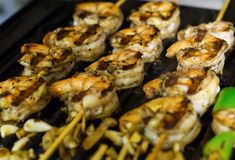 在一个木串特写镜头与格栅条纹,可口的光的被烘烤的虾 免版税图库摄影