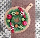 在一个木切板的一个装饰圣诞节花圈 免版税库存照片