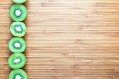 在一个木切板的一半切的新鲜的成熟绿色猕猴桃 自然果子概念 健康饮食题材的背景 免版税库存图片