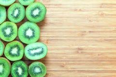 在一个木切板的一半切的新鲜的成熟绿色猕猴桃 自然果子概念 健康饮食题材的背景 免版税图库摄影