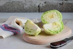 在一个木切板的切好的圆白菜 在最低纲领派样式的切的圆白菜 准备烹调,沙拉,汤 新鲜的未加工的蔬菜 免版税库存图片
