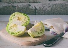 在一个木切板的切好的圆白菜 在最低纲领派样式的切的圆白菜 准备烹调,沙拉,汤 新鲜的未加工的蔬菜 免版税库存照片