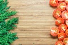 在一个木切板的半和新鲜的绿色莳萝切的新鲜的成熟红色西红柿 自然菜概念 Backgroun 免版税库存图片
