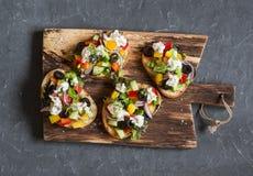 在一个木切板的希腊沙拉样式bruschetta,在黑暗的背景,顶视图 库存照片