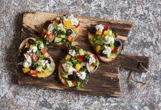 在一个木切板的希腊沙拉样式bruschetta 酒或快餐的可口开胃菜 免版税图库摄影