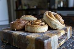 在一个木切板的新近地被烘烤的桂香小圆面包 库存照片