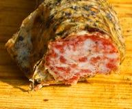 在一个木切板的野公猪蒜味咸腊肠在意大利 库存照片